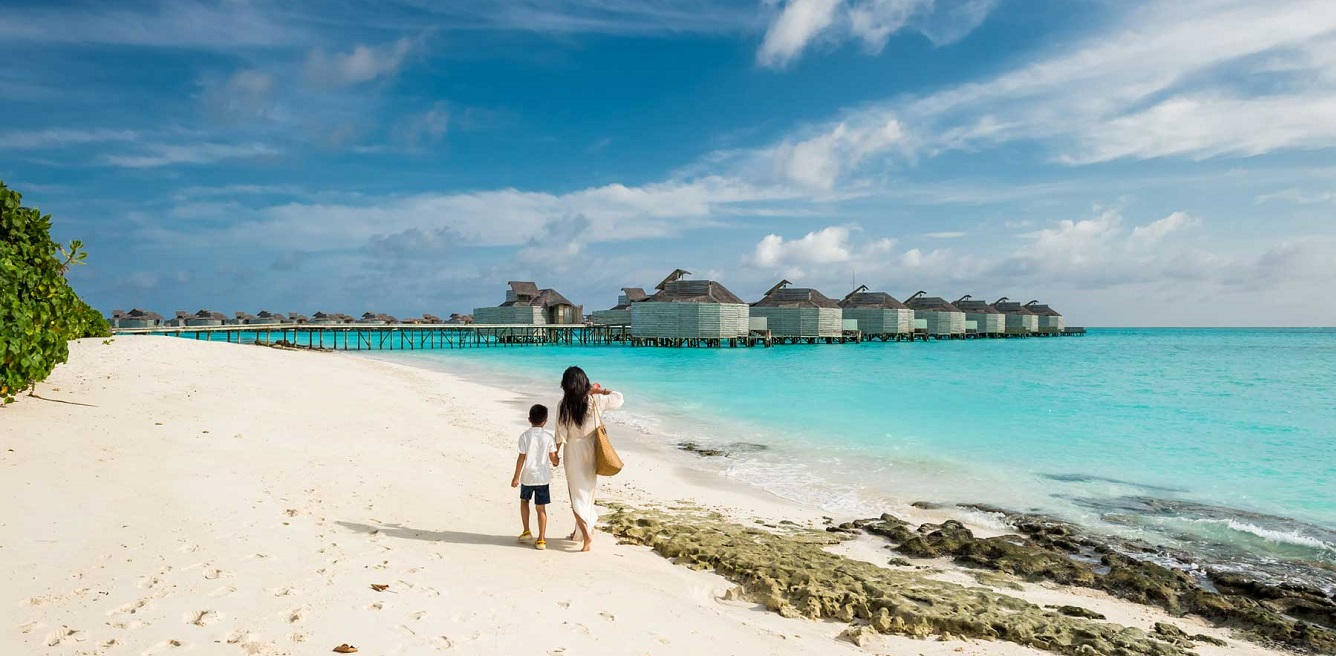 Mother and her son playing on the beach in Maldives island resort.